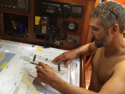 The captain checking his charts and plotting a course prior to departure