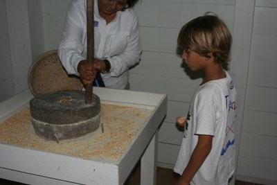 Joshua seeing how corn is ground; he then tries it